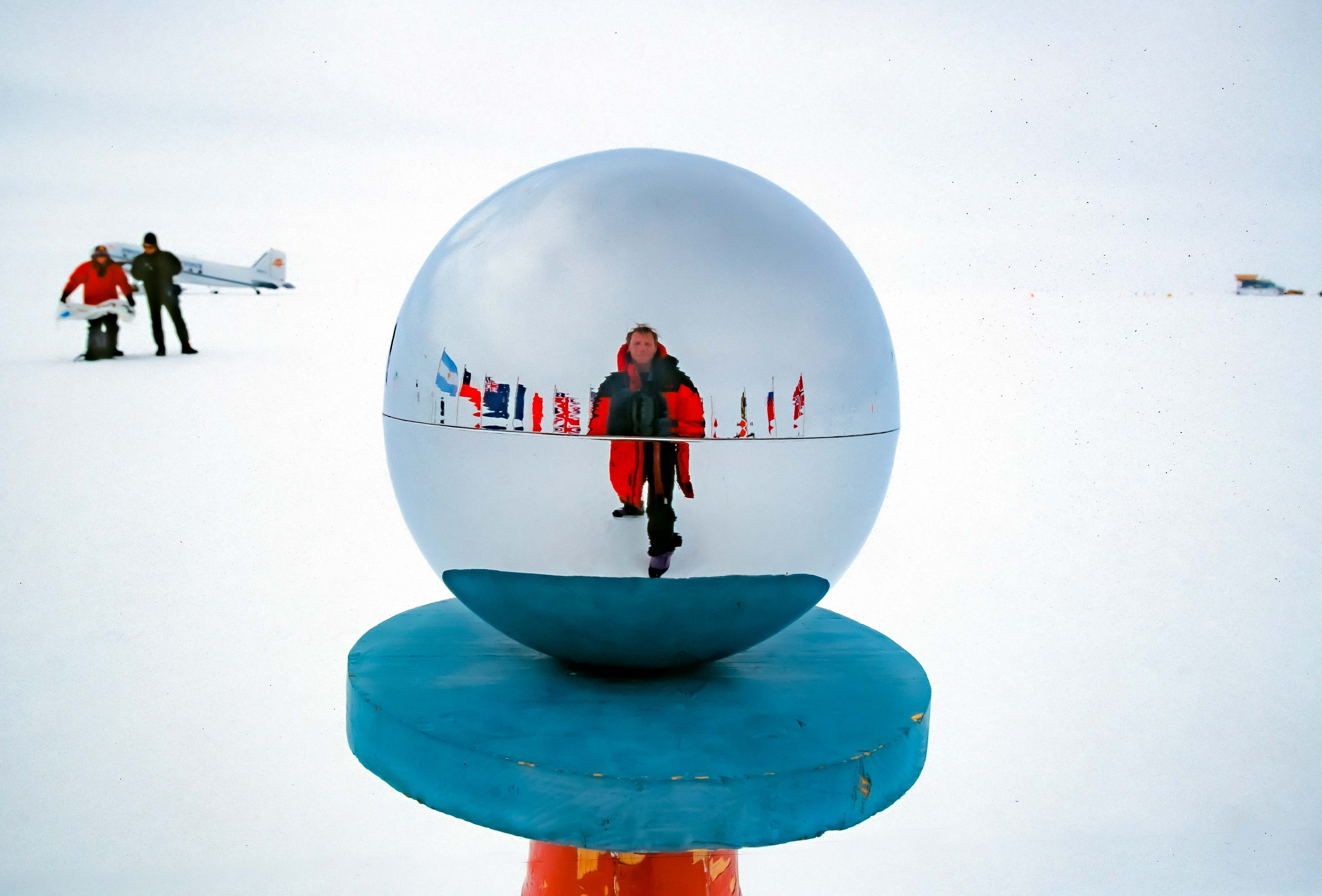 Antarctica, Jeff Shea at South Pole in Globe with Plane, 2001